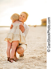 Mother and baby girl hugging on beach at the evening