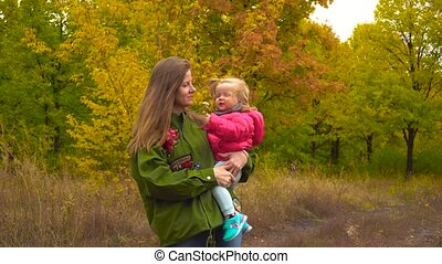 Mother and baby girl in autumn park. Mom telling something...