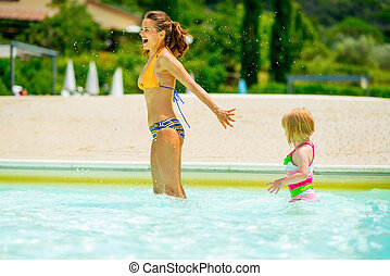 Mother and baby girl playing in pool