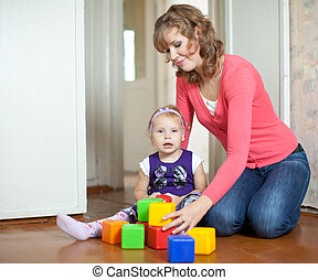 mother and baby girl plays with toy blocks