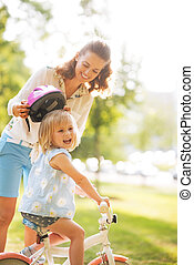 Mother and baby girl riding on bicycle
