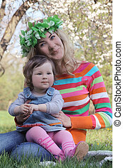 Mother and baby girl sitting under spring tree