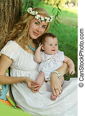 Mother and baby girl sitting under tree