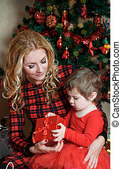 Mother and baby girl under Christmas tree with gift-box