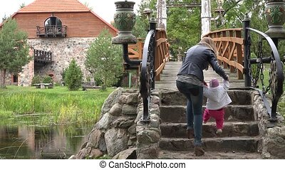 mother and baby girl walk on stone stair bridge in park.