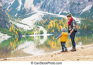 Mother and baby having fun time on lake braies in south tyrol, i