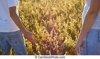 mother and baby hold hands in a field
