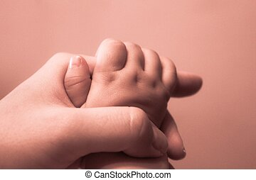 Mother and baby holding hands