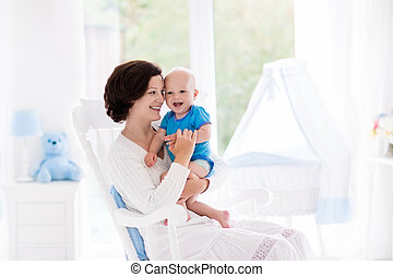 Mother and baby in bedroom - Mother and baby at home. Young...