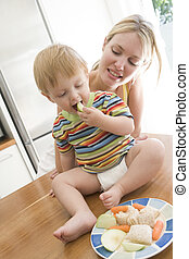 Mother and baby in kitchen eating fruit and vegetables