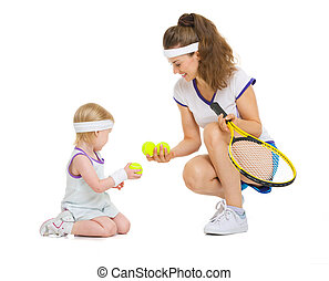 Mother and baby in tennis clothes playing