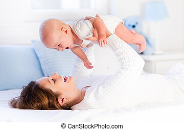 Mother and baby on a white bed - Mother and child on a white...