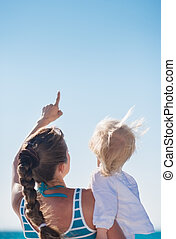 Mother and baby on beach pointing up on copy space. Rear view