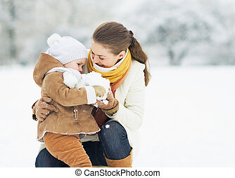 Mother and baby playing in winter park
