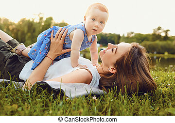 Mother and baby playing on grass in park.