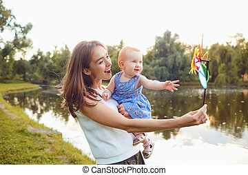 Mother and baby playing on grass in summer park
