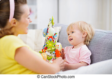 Mother and baby playing with Easter decoration