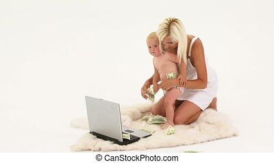 Mother And Baby Playing With Money And Laptop