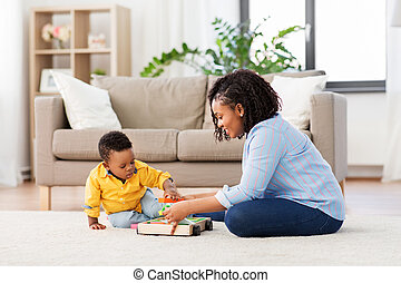 mother and baby playing with toy blocks at home