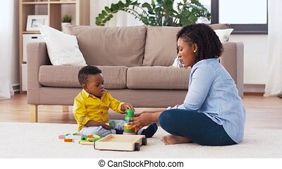 mother and baby playing with toy blocks at home - childhood,...