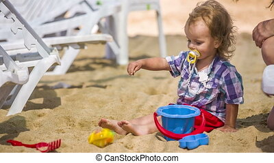 Mother And Baby Playing With Toys In Sand