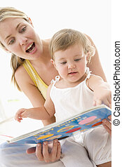 Mother and baby reading book indoors and pointing