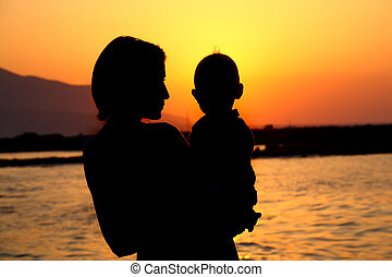 silhouette of a mother holding a baby over a sunset background