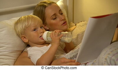 mother and baby son reading a book in bed before going to...