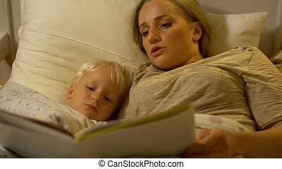mother and baby son reading a book in bed