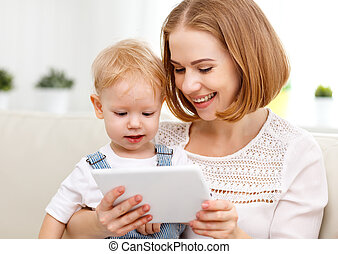 Mother and baby son with a tablet computer at home