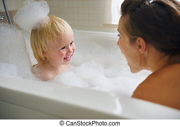 Mother and baby taking bath and playing with foam