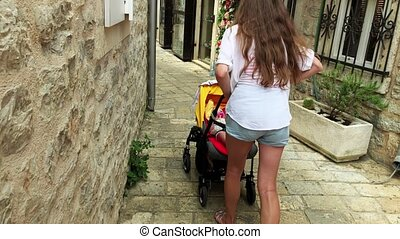 Mother and baby travel along narrow old town street with a...