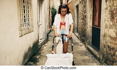 Mother and baby traveling in Mediterranean old town with a stroller on vacation
