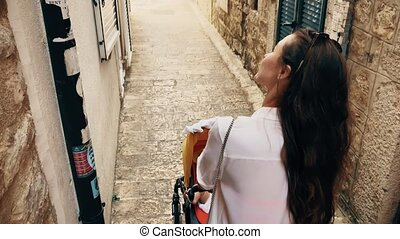 Mother and baby walk in Montenegro old town with a stroller