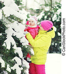 Mother and baby walking in snowy forest