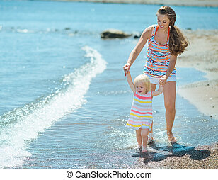 Mother and baby walking on beach