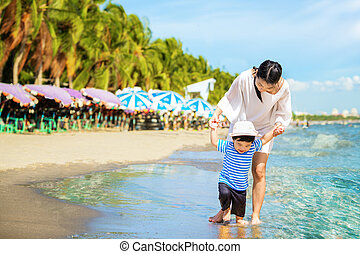 Mother and baby walking on the beach