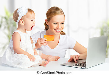 mother and baby  with a laptop and credit card