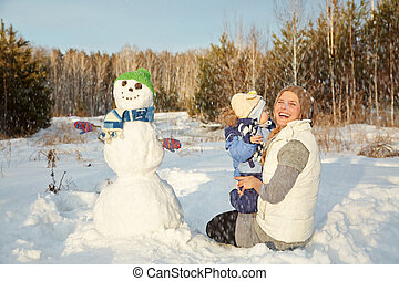 mother and baby with snowman