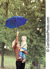 Mother and baby with umbrella walking in autumn day, soft vintag