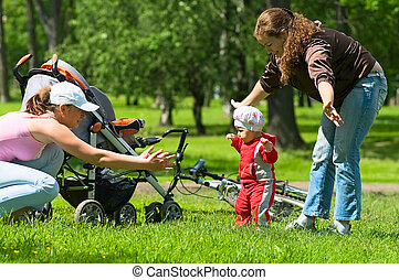 Mother and babysitter learn child to do first steps.