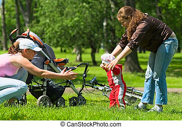 Mother and babysitter learn to walk baby. - Two women help ...