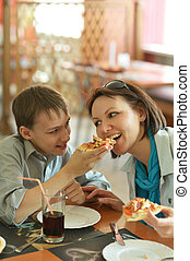 Mother and boy eating pizza