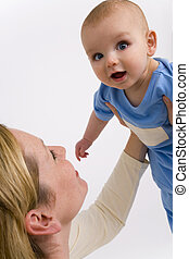 A young mother holds her child high in the air as he smiles and looks to the camera