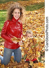 mother and child among fallen leaves