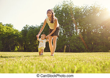 Mother and child are walking in the park at sunset .