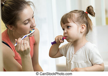 Mother and child brushing teeth together in the morning - dental care concept