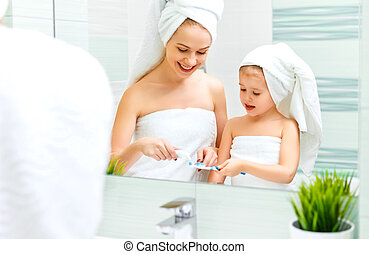 Mother and child daughter brush their teeth with  toothbrush