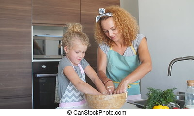 Mother and child daughter girl having fun while making dinner at the kitchen.