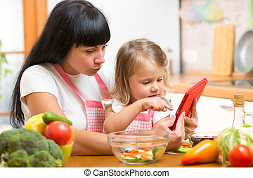 Mother and child daughter prepare recipe in kitchen.